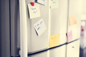 Post-it notes on a fridge door.
