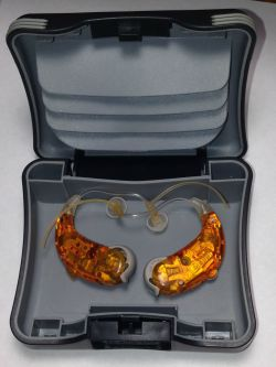 A pair of orange hearing aids sitting in a case